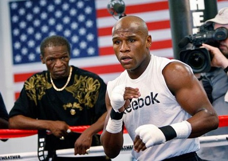 Floyd Mayweather Sr.. looking at his $565 million net worth son in the ring wearing a reebok vest from outside his corner.
