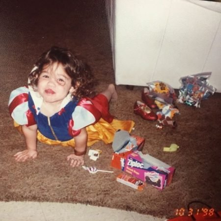 Madison McLaughlin at two years old wearing a Snow White costume and lying in the floor.