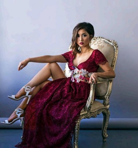 Brenda Song in a chair like a Royal in red dress. Her Net worth is staggering.