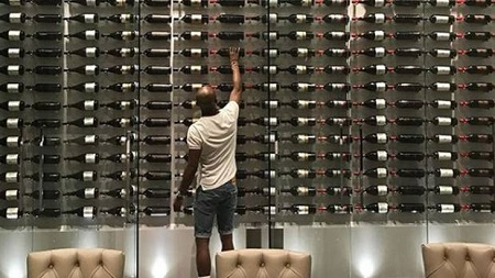 Floyd Mayweather reaching for a bottle of wine from his wine cellar in his home