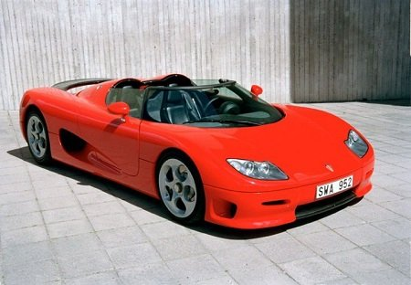 A red Koenigsegg CC8S parked in a concrete floor in front of a wall.