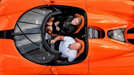 Christian von Koenigsegg and his wife, Halldora von Koenigsegg looking at the camera above their head while sitting on their red Koenigsegg car.