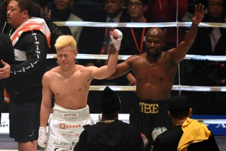 Floyd Mayweather holding Tenshin's hand in the air as he signals for victory, but Tenshin is grunting with his other hand down. The fight increased Floyd's net worth by $9 million.