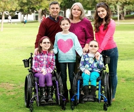 The McLaughlin family pictures. Two of her three sisters suffering from a rare disease sitting in the front on wheelchairs. Her Parents to her right.