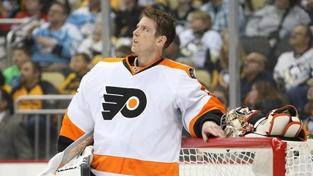 Mason leaning with left hand on the ice hockey post as he looks up to the right with no helmet on, in the white dominant Flyers dress.