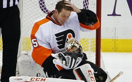Mason looking distressed with his left hand on his head and the right with the helmet and gloves on, sitting in front of the rink post.