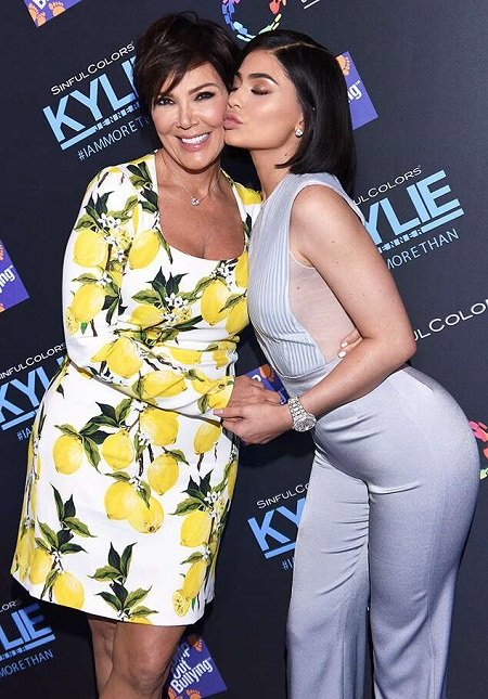 Kylie (right) kissing her mother Kris on the cheek as they pose for the launch of her Kylie Cosmetics.