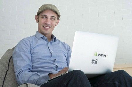 Tobi Lutke sitting on a couch with a laptop on his lap with the 'Shopify' sticker and smiling at the camera.