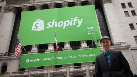 Shopify CEO Tobi Lütke outside the New York Stock Exchange. A huge green board with Shopify written on it is displayed behind him.