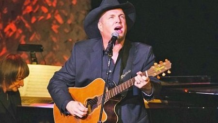 Garth Brooks singing his heart out with a guitar and a signature hat.
