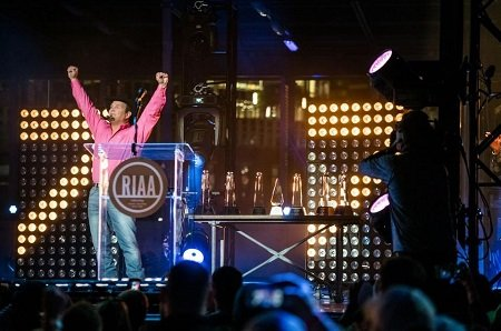 Garth Brooks received his 7th Diamond Certificate from the RIAA in 2016. Pink shirt and thowing his hands up in the air.