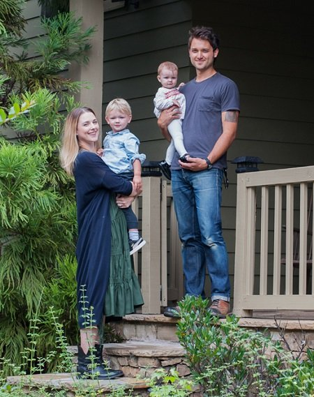 Alexandra Breckenridge and husband Casey Hooper each holding a baby in their hands at the front porch of their Atlanta home.
