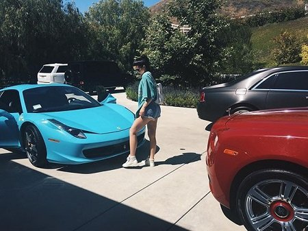 Kylie Jenner in front of the blue 458 Spyder.