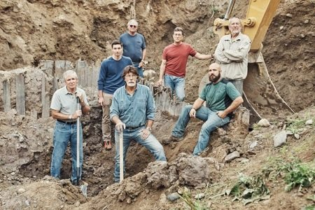 'The Curse of Oak Island' crew posing in the dirt in front of a crane.