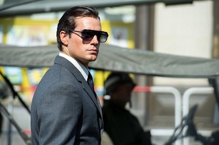 Henry Cavill wearing suit and glasses like James Bond.