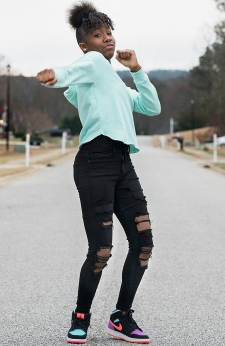 Jalaiah Harmon on the streets of her hometown posing a move from her Renegade Dance.