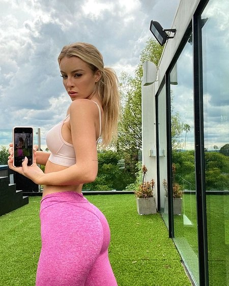 Daisy Keech showing her body with a camera phone showing the selfie clicked.