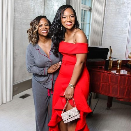 Kandi Burruss with her teenage daughter RIley in a red dress for her prom.