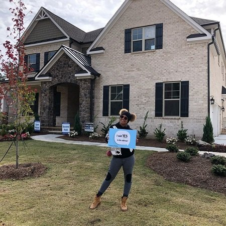 "Eva Marcille posing on the lawn in front of her lovely new beige house holding a sign that said, ""I said YES to the address!"""