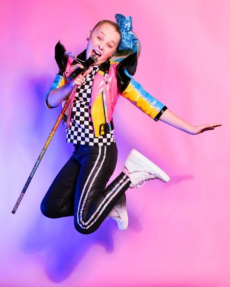 JoJo Siwa jumping up in the air with a mic stand in her hand.