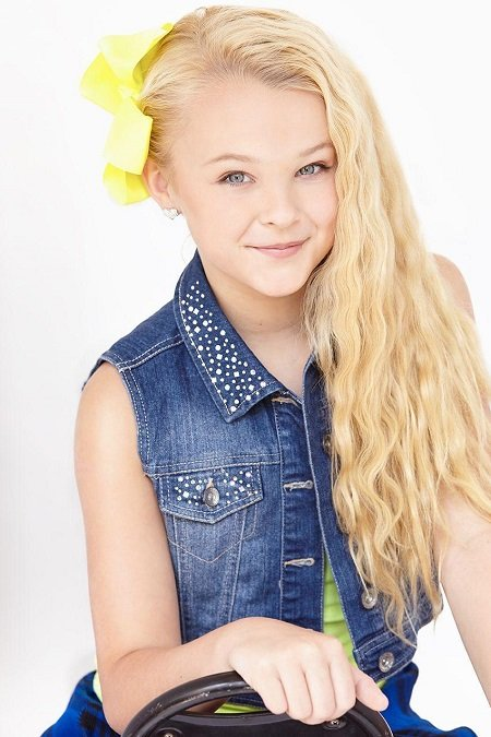 JoJo Siwa without her ponytail but with a yellow bow.