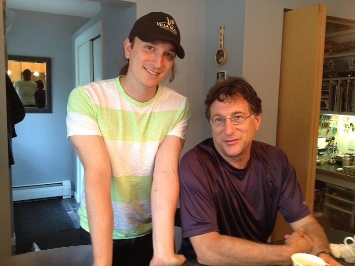 Marty Lagina sitting with hands on a table as his son Alex Lagina stands beside him looking at the camera.