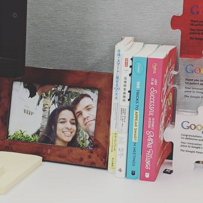 A photo of Sarah Cooper and her husband on a desk with her three released books.