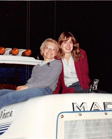 Julie Nolke's relative with her mom Cheryl Nolke on the hood of a semi-truck.