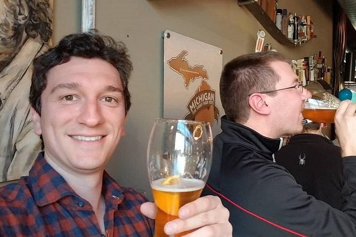 Alex Lagina holding a glass of beer in celebration.