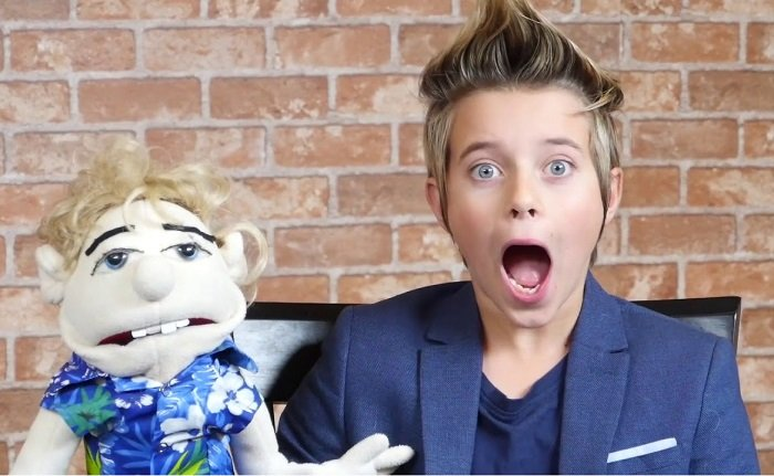 Gavin Magnus holding a puppet & gasping his breath.