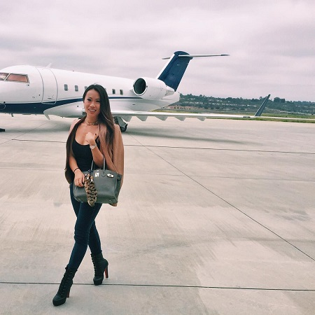 Kelly Mi Li in front of her private jet.