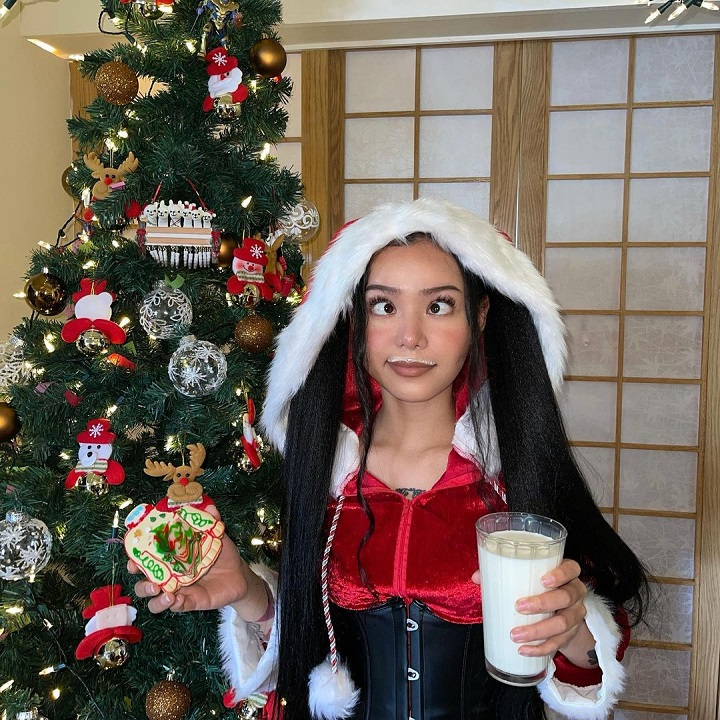 Bella Poarch in a Santa costume except the beard holding a glass of milk and making her signature face.