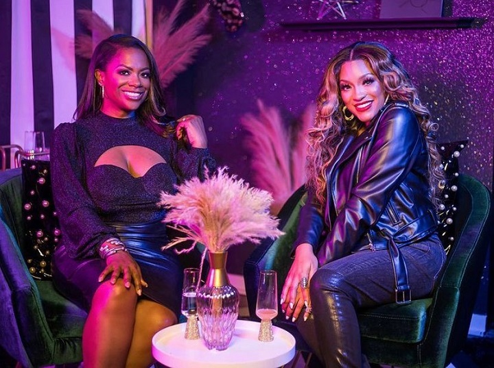 Drew Sidora and Kandi Burruss of Real Housewives of Atlanta sitting in chairs posing for the photo.