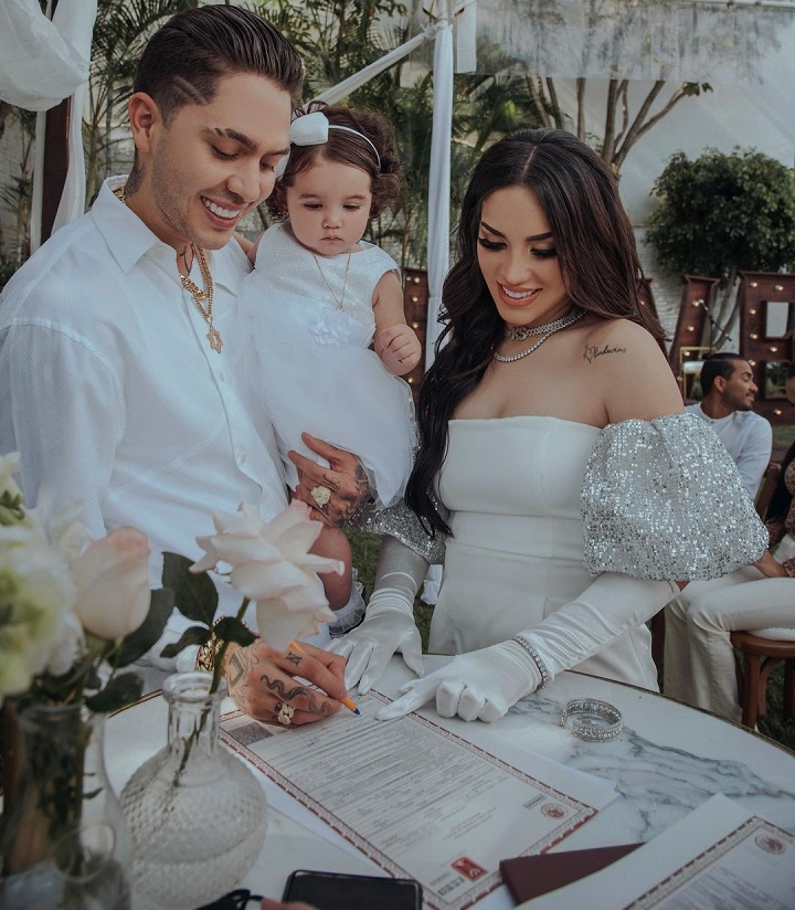 Kimberly Loaiza with her husband, JD Pantoja, signing the marriage documents while holding their daughter.