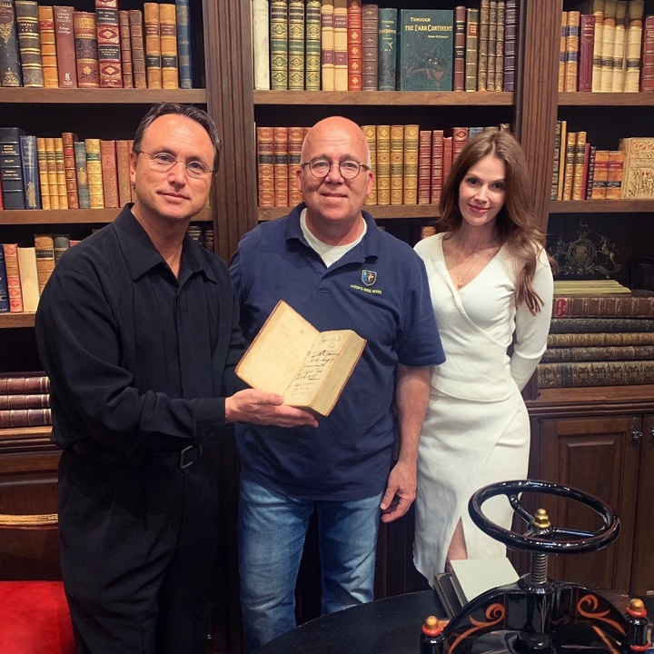 Brandon Fugal (left) with his wife (right) and a librarian (center) at Moon's Rare Books.