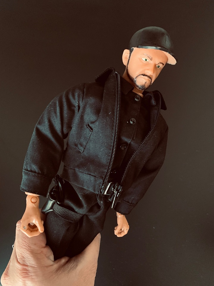 Bryant Arnold's action figure in Brandon Fugal's hand.