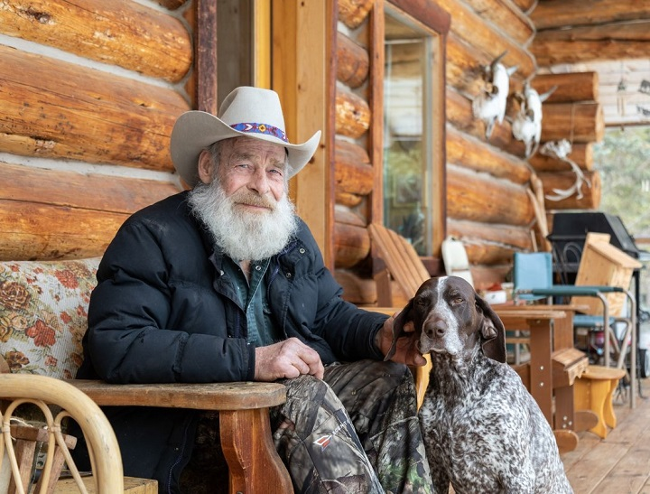 Tom Oar pictured with his German short hair pointer, Elli, sitting out the front door of his home.
