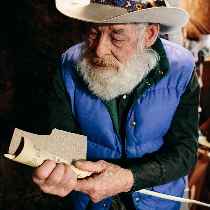 Tom Oar rubbing sandpaper on one of his artifacts.