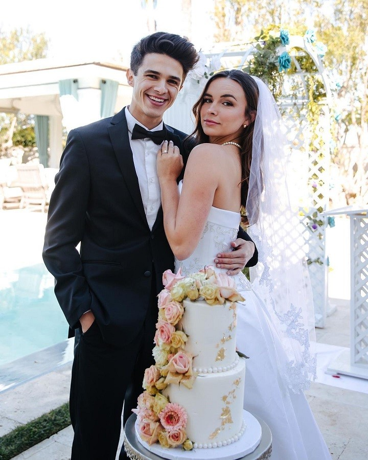 Brent Rivera (Left) and Pierson Wodzynski (Right) posing for their pretend-wedding in behind the cake.