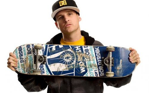 Rob Dyrdrek, who has a net worth of $50 million, holding a skateboard to his chest with the wheels shown and wearing a cap.
